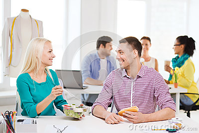 Smiling Fashion Designers Having Lunch At Office Stock