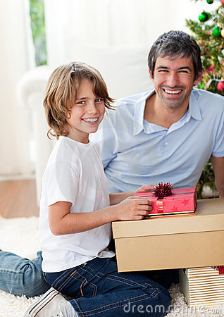 Smiling father and his son opening Christmas gifts