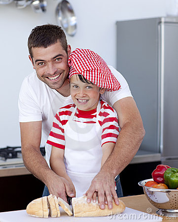 Smiling father and son cutting bread