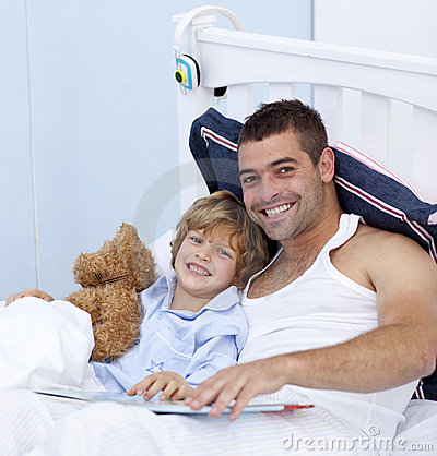 Smiling father and son reading a book in bed