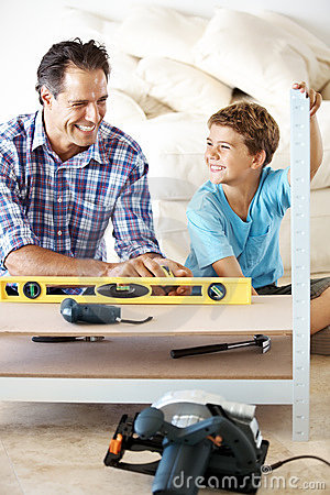 Smiling father and son working in workshop