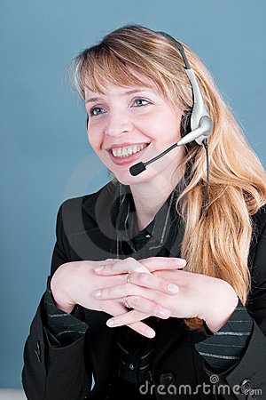 A smiling female answering the telephone