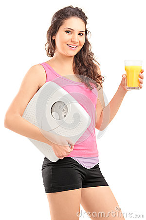 A smiling female athlete holding a weight scale and glass of ora