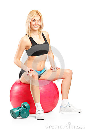 A smiling female athlete resting on a fitness ball