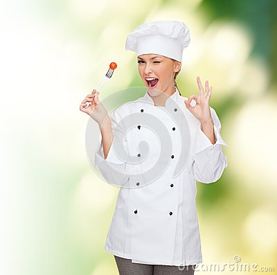 Free Smiling Female Chef With Fork And Tomato Stock Image - 38574171