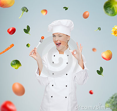 Free Smiling Female Chef With Fork And Tomato Royalty Free Stock Photography - 53185037