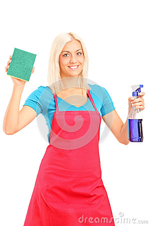 Smiling female cleaner holding a sponge and spray