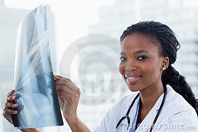 Smiling female doctor looking at a set of X-rays