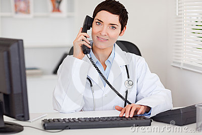 Smiling female doctor making a phone call