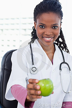 A smiling female doctor showing an apple