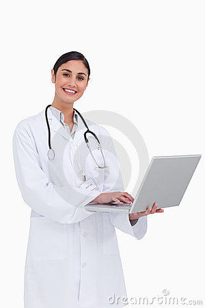 Smiling female doctor working on her laptop