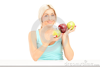 A smiling female holding apples and posing on a table