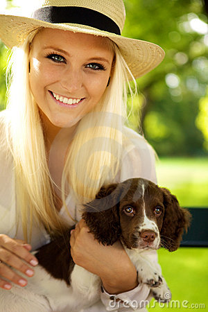Smiling female holding her puppy.