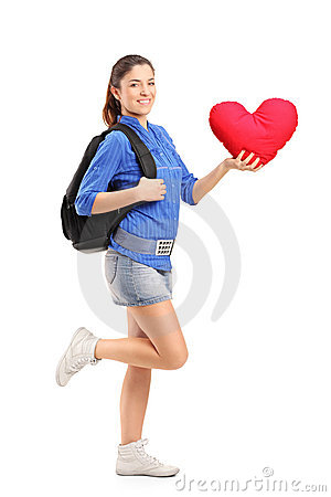 Smiling female holding a red heart shaped pillow