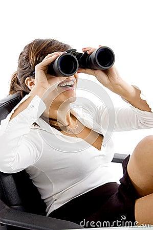 Smiling female looking through binoculars
