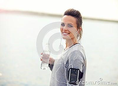 Smiling Female Runner Holding a Bottled Water