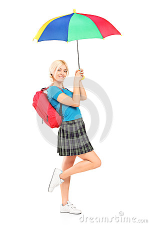 Smiling female with school bag holding umbrella