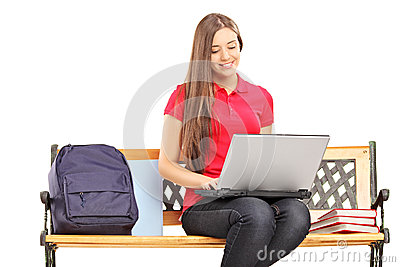 Smiling female student sitting on a wooden bench and working on