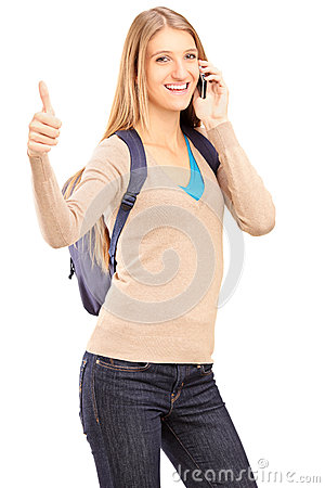 A smiling female student talking on a phone and giving thumb up