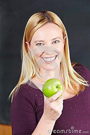 Smiling female teacher with apple