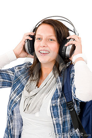 Smiling female teenager enjoy music headphones