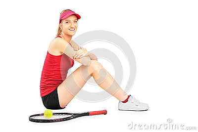 A smiling female tennis player resting after a match