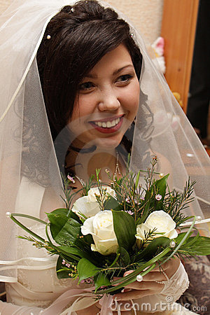 Smiling fiancee with flowers in the hands