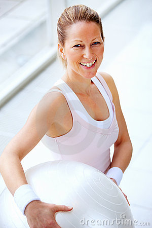Smiling fit mature female holding  a fitness ball
