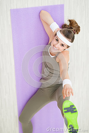Smiling fit woman on fitness mat making gymnastics