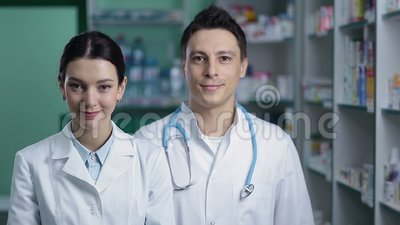 Smiling friendly pharmacists working in pharmacy stock video footage