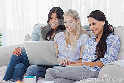 Smiling friends looking at laptop together