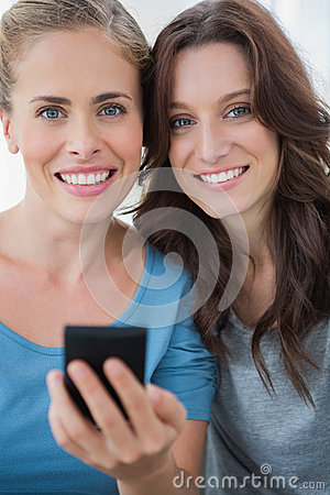 Smiling friends with mobile phone