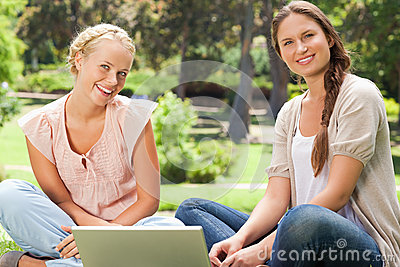 Smiling friends sitting in the park with a laptop