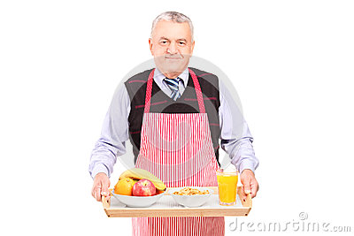 A smiling gentleman in apron carrying a tray with drinks and food