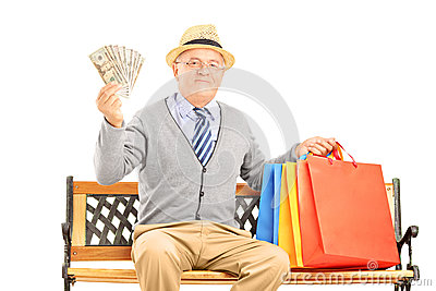 Smiling gentleman sitting on a bench with bags and holding money
