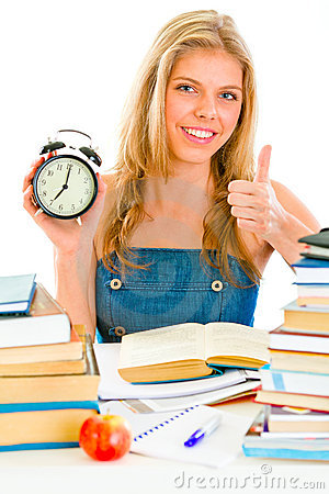 Smiling girl with alarm clock showing thumbs up