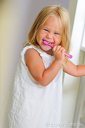 Smiling girl in bathroom brushing teeth