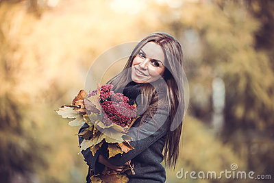 Smiling girl with bouquet in autumn park