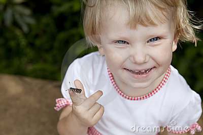 Smiling girl with a butterfly on the finger