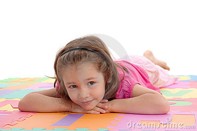 Smiling girl child resting on kids alphabet floor
