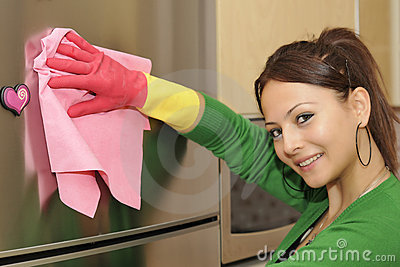smiling girl cleaning the house - refrigerator