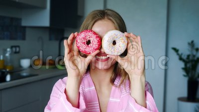 Smiling girl covering his eyes with glazed donuts. Pretty woman having fun. In kitchen. Sweet cookie. Close up girl fool around with doughnuts at home stock video
