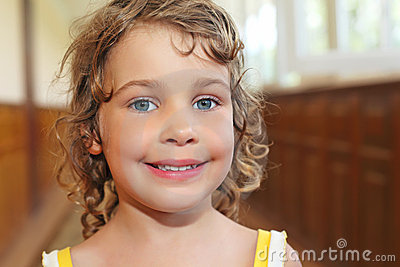 Smiling girl with curly hair in corridor