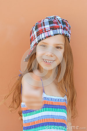 Smiling girl in dress raises thumbs-up