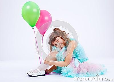 Smiling girl embracing knees