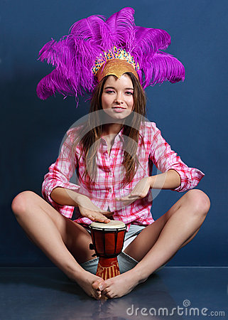 Smiling girl in hat with feathers sits on floor and beats drum