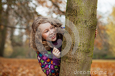 Smiling girl hiding behind a tree