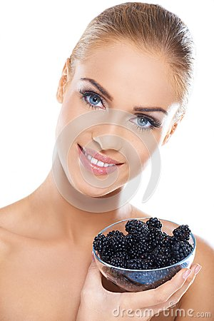 Smiling girl holding blackberries on hand