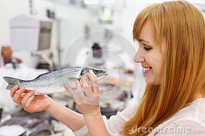 Smiling girl holds fish in store