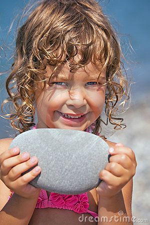 Smiling girl holds in hands pebble on seacoast